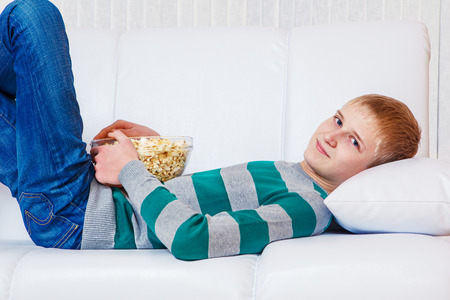 Teenager lies on the sofa and watches TV with a large glass popcorn bowl photo