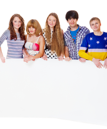 teenage girl happy: Five teenage girls and boys hold blank paper board Stock Photo