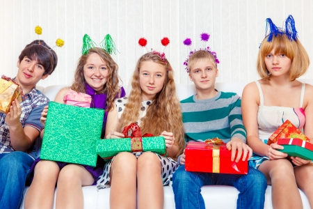 Cheerful teenagers hold party presents photo