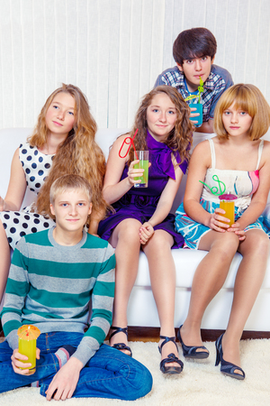 Group of cheerful teenagers with beverages in a living room photo