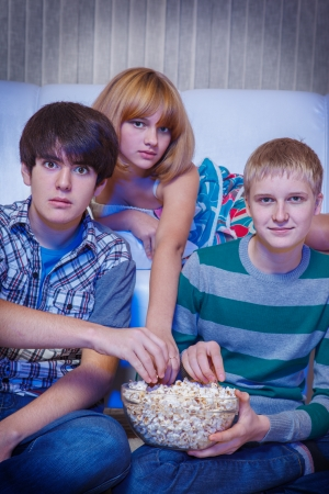 eating popcorn: Three friends watching movie in darkness and eating popcorn Stock Photo
