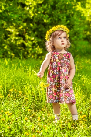 Curly girl with a spring dandelion headwreath photo