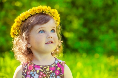 Portrait of a preschool girl with yellow flowers headwreath on photo