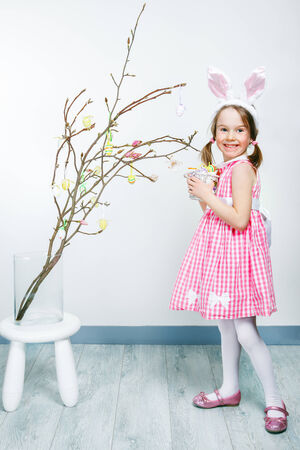 decorates: Girl holds basket with Easter eggs and decorates magnolia branch Stock Photo