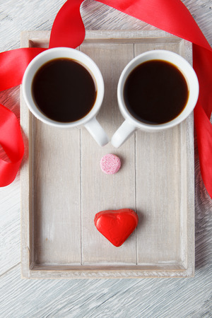 Funny face on the wooden tray made with coffee cups and candies photo