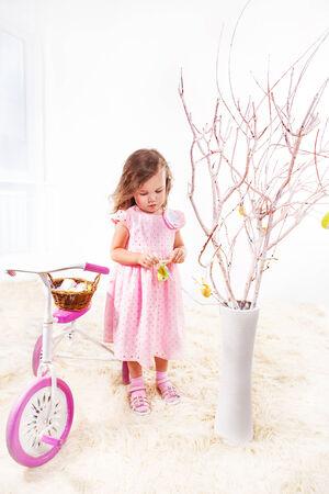 easter tree: Preschool girl in pink dress decorating Easter tree