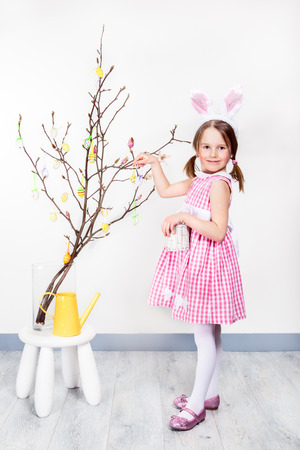 easter tree: Preschool girl with bunny ears decorating Easter egg tree