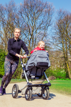 Sportive mother jogging with her smiling toddler in a buggy photo