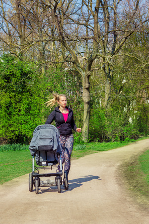 buggy: Active young woman jogging in a park with a baby buggy Stock Photo