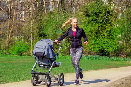 公園でエクササイズをしながら若い女性押す赤ん坊を乗せた乳母車を笑顔