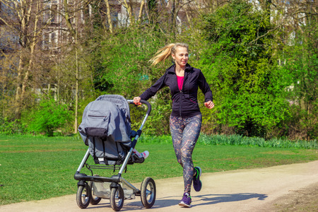 Smiling young woman pushing baby buggy while exercising in a park photo