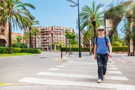pedestrian crossing: Tourist with a backpack crossing the road in Valencia, Spain Stock Photo