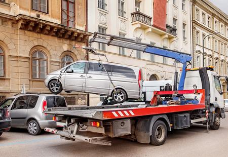 Carro attrezzi rimuove una vettura parcheggiata illegalmente dalla strada Archivio Fotografico - 28449165