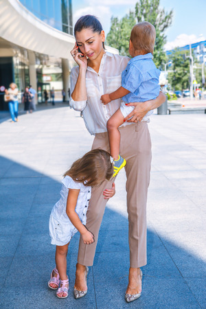 blonde mom: Business mother speaking over the cellphone, with two kids Stock Photo
