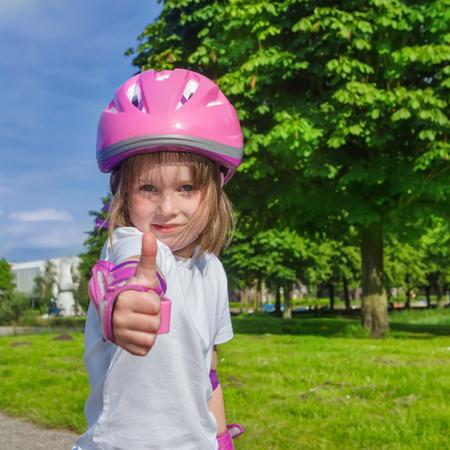 sportwear: Preschool girl in protective sportwear showing thumb up