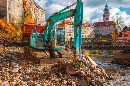 Excavator on the bank of Vlatava river, putting stones to the truck photo
