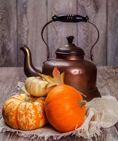 Autumn still life: tin kettle and pumpkin with leaves photo