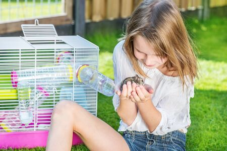 hamster: Girl sitting in the backyard with a small hamster in palms