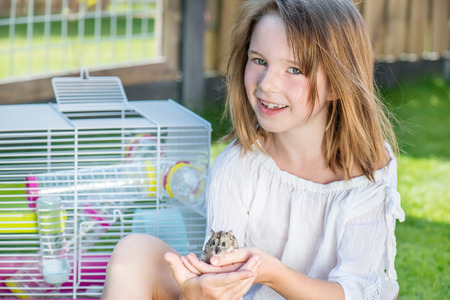 cute hamster: Happy little girl sitting in the backyard with a small hamster in hands