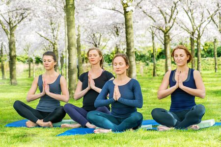 opening up: Four young women practising Lotus Pose for opening up the hips and creating flexibility in the ankles and knees Stock Photo