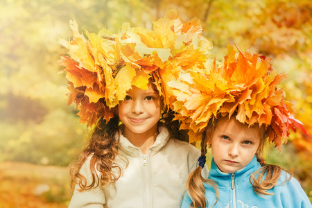 family fall: Two cute embracing friends in a yellow autumnal park