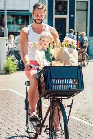 holland: Father cycling with his toddler daughter,  flowers and vegetables in his bicycle basket Stock Photo