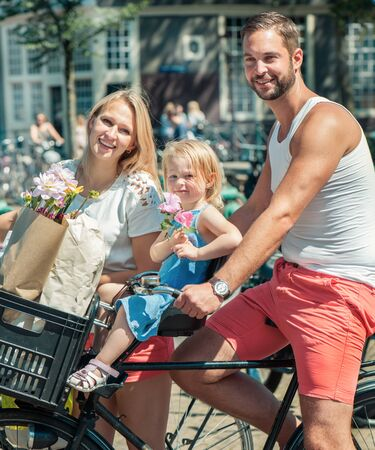 fun day: Young smiling family riding bicycles at the streets of Amsterdam