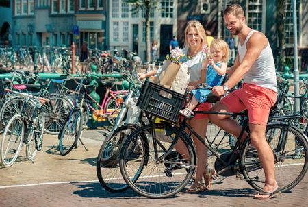 Los padres jóvenes en bicicleta con su pequeña hija a lo largo de las calles de Ámsterdam