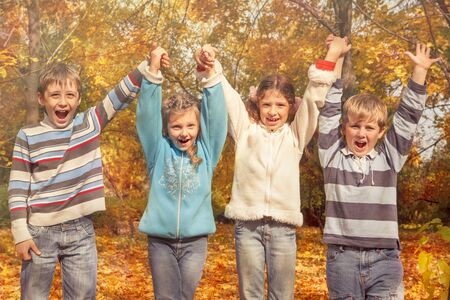 Group of cheerful friends holding hands in the autumnal park photo