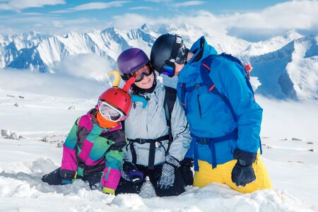 protective helmets: Young family in ski outfit and protective helmets high in the mountains
