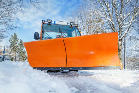 plough machine: Orange snowplough with big blade cleaning the streets from snow Stock Photo