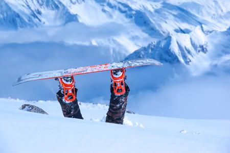 deep freeze: Legs of a snowboarder stuck in deep snow upside down Stock Photo