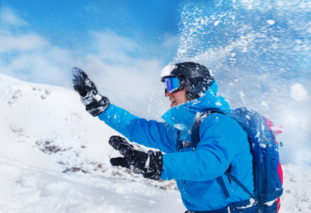 snowballs: Man in helmet and googles playing snowballs in the mountains Stock Photo