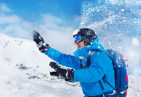 neve palle: Uomo in casco e occhiali a giocare palle di neve in montagna