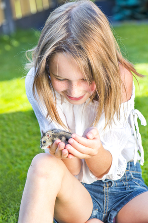 small girl: School girl sitting in the backyard with a small hamster in palms Stock Photo