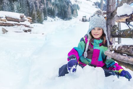palisade: Smiling girl sitting in deep snow near wooden palisade