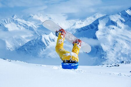 snow white: Legs of a snowboarder stuck in deep snow upside down Stock Photo