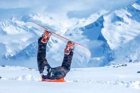 Legs of a snowboarder stuck in deep snow upside down Stockfoto