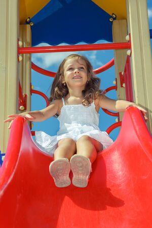 Riendo niña preescolar sentado en la parte superior de una diapositiva de los niños, en el parque infantil