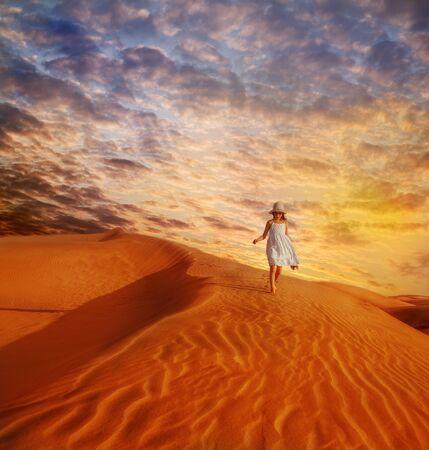 dune: Little girl in white dress and hat walking down the sand dune in desert, at sunset