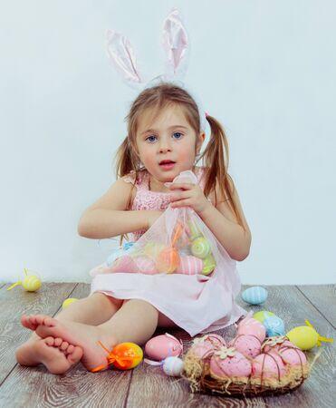petite fille avec robe: enfant d'âge préscolaire avec des oreilles de lapin de Pâques à jouer avec des oeufs colorés Banque d'images