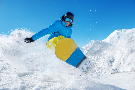 snowboarder jumping: Active snowboarder jumping in winter mountains Stock Photo