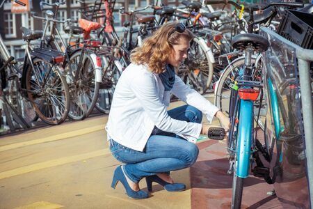 holland: Woman unlocking the bicycle at the bike parking Stock Photo