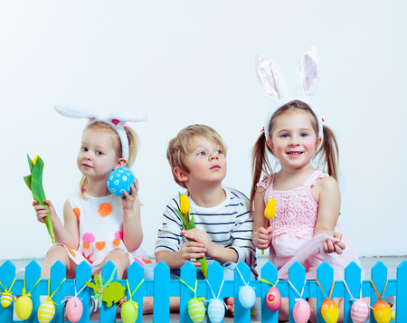 preschoolers: Group of attractive preschoolers sitting behind a blue fence decorated with Easter eggs Stock Photo