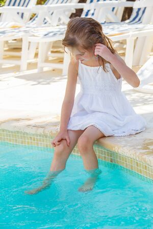girl sit: Girl in a white dress sitting by an outdoor swimming-pool, with her legs in water