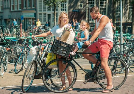 netherlands: Young parents cycling with their little daughter at the streets of Amsterdam