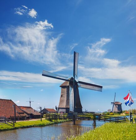 dyke: Old mills with Dutch flags standing in front of the bridge over the dyke. Mills are one of the tourists attractions in the Netherlands