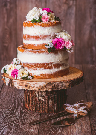 Homemade two-layered wedding naked cake decorated with flowers on a wooden cut stand Stockfoto