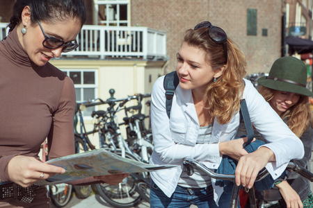 netherlands: Female tourists looking at the map in Amsterdam, capital of the Netherlands