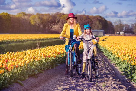 dutch girl: Mom and daughter riding bikes along tulip rows on a sunny day Stock Photo